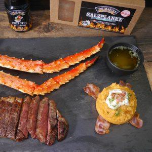 Süßkartoffelpüree, Crap legs und Steak auf Schiefplatte mit Salzplanke und Gewürz im Hintergrund