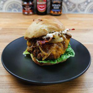 Irish Cheddar Burger mit WonderGreen Schmorzwiebeln auf schwarzem Teller