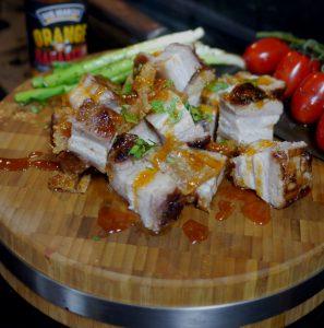 crispy asia schweinebauch auf holzplatte