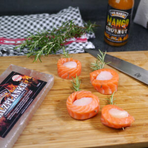 Jakobsmuschel Lachswrap auf Salzplanke auf Holzbrett neben Messer und Salzplanke